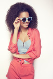 Fototapety Laughing African young woman with an afro hairstyle wearing sunglasses and pastel stylization