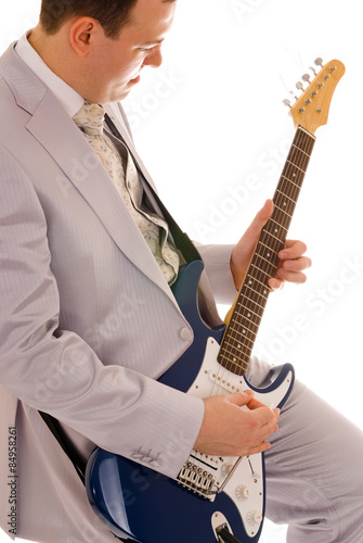 Poster man in white suit playing guitar