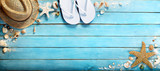 seashells on blue wooden plank with straw hat and flip-flop
