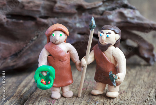 Poster Plasticine world - caveman with spear and stone ax and woman