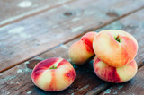 Fresh Saturn peaches on old board