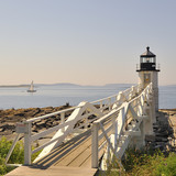 Marshall Point Lighthouse Port Clyde Saint George Maine with sailboat seen with the walkway looking toward Penobscot Bay. Square format with copy space.