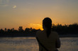 Постер, плакат: Silhouette of a woman while observe sunset by the river