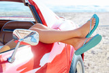 Fototapety Relaxed woman legs in a car window on the beach