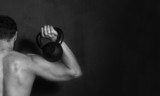 Bodybuilding. Strong young man doing exercise with dumbbell on black background - 85243082