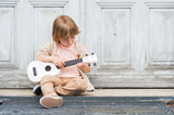 Fototapety Little happy boy plays his guitar or ukulele, sitting by the wooden door outdoors