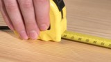 Carpenter worker using, roulette measuring, on wooden plank