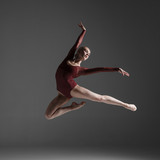 Fototapety Young beautiful modern style dancer jumping on a studio
