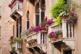 Fototapeta Beautiful old building balconies with colorful flowers