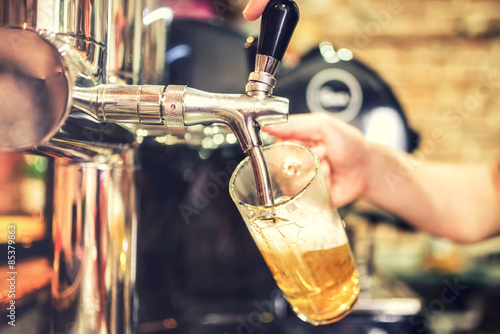 barman hand at beer tap pouring a draught lager beer serving in a restaurant or Poster