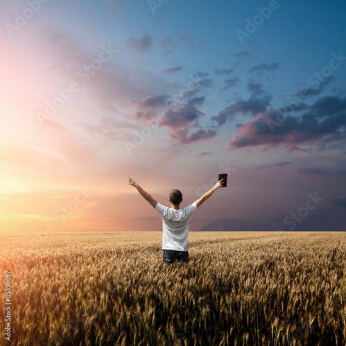 Zdjęcia na płótnie, fototapety, obrazy : man holding up Bible in a wheat field