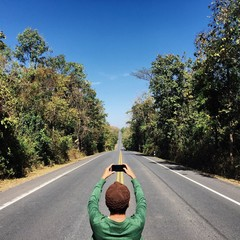Man take a photo with the long road