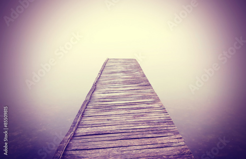 Vintage filtered picture of old wooden pier and dense fog. Poster