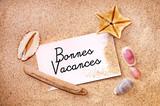 Fototapety Bonnes vacances écrit sur une carte dans le sable et coquillages