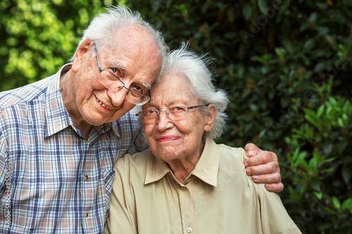Couple de personnes âgées dans le jardin Poster