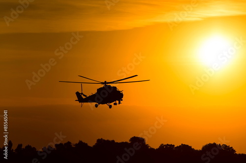 Poster silhouette of military helicopter at sunset