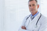 Fotoroleta Confident male doctor looking at camera with arms crossed