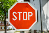 Old, weathered and violated stop sign in the street poster