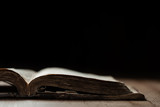 Image of an old Holy Bible on wooden background in a dark space with shallow depth of field