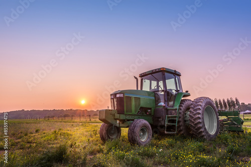 Fotobehang Trekker Tractor in a field on a Maryland farm at sunset
