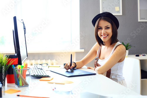 Young female designer using graphics tablet while working  Poster