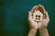 Hands holding little wooden house on blackboard background. Symb