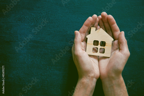 Hands holding little wooden house on blackboard background. Symb