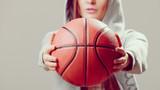 Fototapety Sporty teen girl in hood holding basketball.