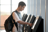 Fototapety Man doing self-registration for flight
