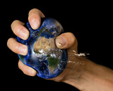 Squashed Earth in a clenched fist. A conceptual image for the human impact on the planet.