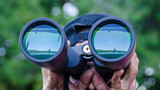 Man views swimmers on a lake during a race that are reflected on the lenses of his binoculars - 85758465