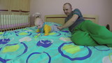 young father play with his four month baby daughter in bedroom at home. Happy family and fatherhood concept. 4K UHD wide angle shot. poster