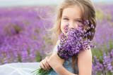 Fototapety Happy little girl in lavender field with bouquet