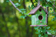 Green birdhouse hanging from tree