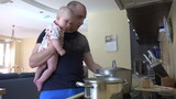young father together with baby girl  prepare dinner in big pot. Father taste the soup for salt. Fatherhood and baby care at home. Static tripod shot. 4K UHD video clip. poster