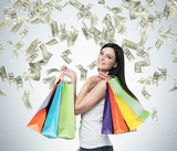 Beautiful smiling brunette woman with the colourful shopping bags from the fancy shops. Falling dollar notes from the ceiling.