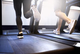 Fototapety Legs of Fit Couple Exercising on Treadmill Device
