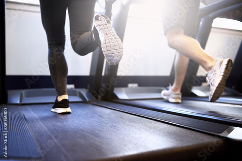 Juliste Legs of Fit Couple Exercising on Treadmill Device