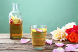 Fototapeta succo acqua di rose in bicchiere su tavolo di legno