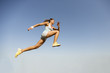 Young woman taking long jump