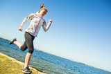 Fototapeta Young woman running near the river at sunny day. Sportswoman
