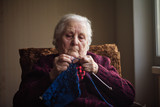 The old woman sits at home and knits garments.