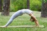 girl doing yoga and gymnastics on the grass