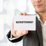 Businessman holding up a small white card saying Questions