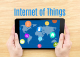 Hand holding tablet with Internet of things (IoT)  word on woode poster