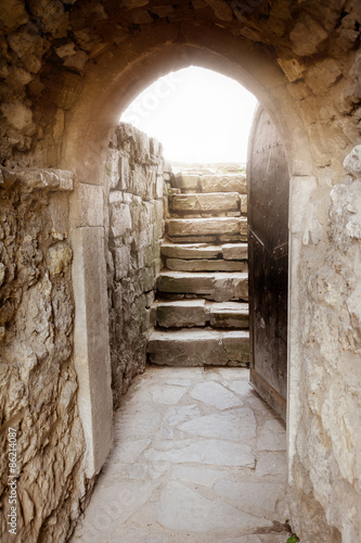 Stone wall with open door and rays of light behind © tainar