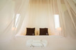 white mosquito net over a bed in a luxurious hotel