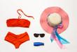 Orange bikini swimsuit and accessories on white background.