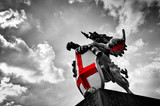 St George dragon statue in London, the UK. Black and white, red flag, shield. - 86329472
