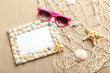 Frame of sea shells with sunglasses on beach sand